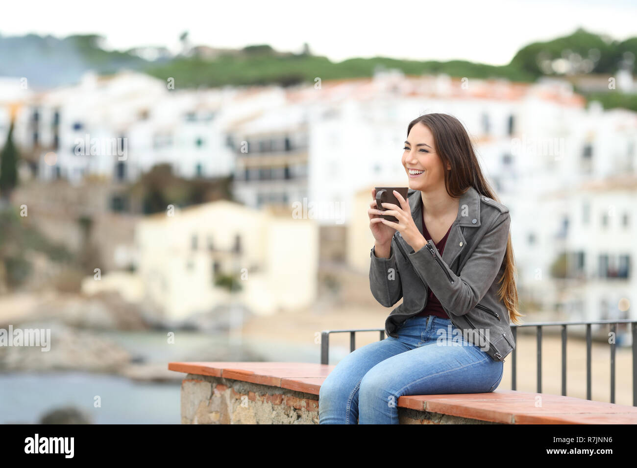 Happy woman sitting on a ledge drinking coffee and looking away in a coast town - Stock Image