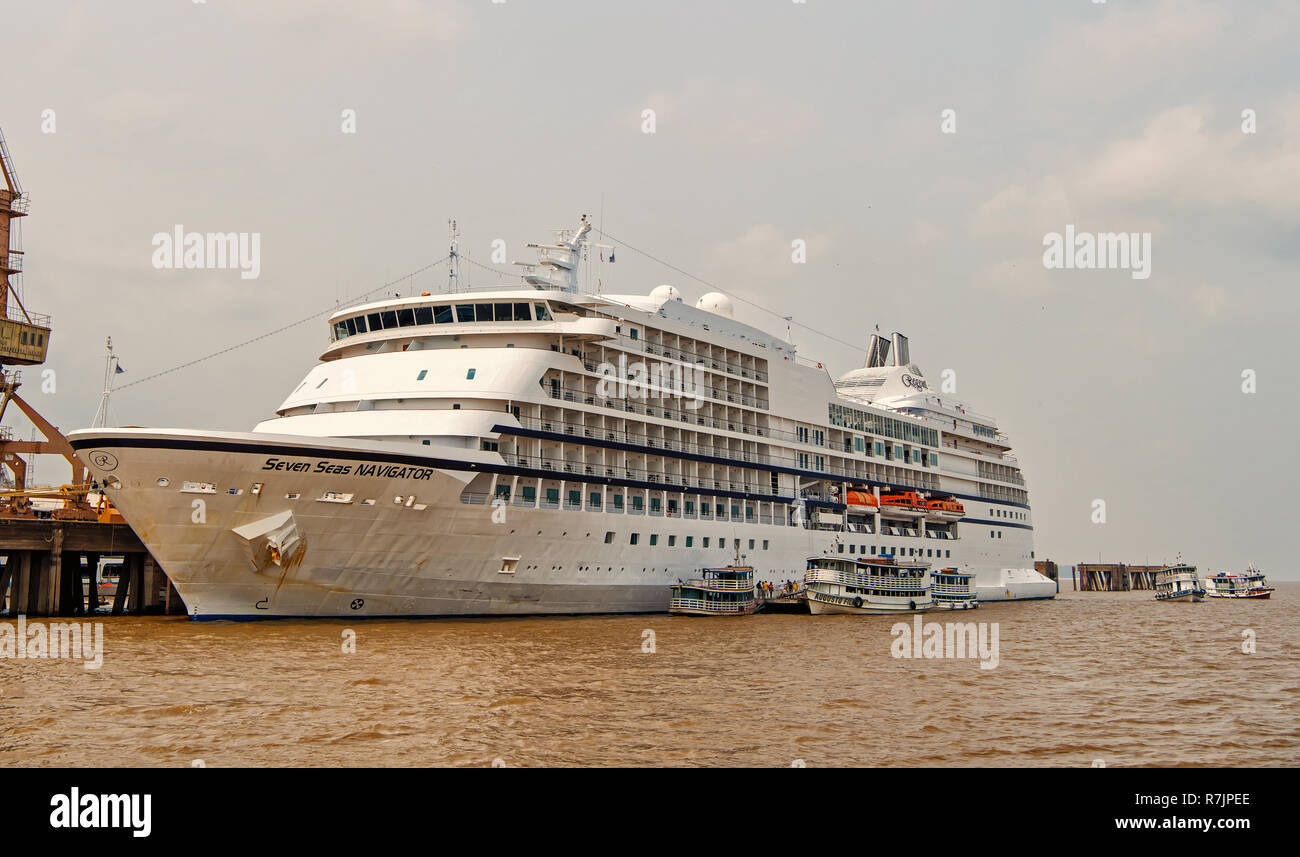 Santarem, Brazil - December 02, 2015: Seven Seas Navigator cruise ship docked at sea harbor on grey sky background. Luxury lifestyle concept. Tourist destination and trips. Travel and travelling - Stock Image