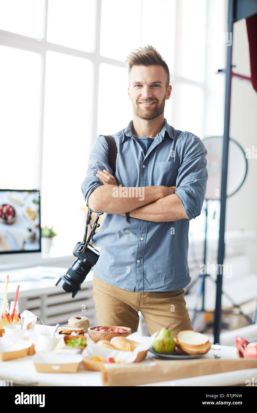 Waist up portrait of smiling photographer looking at camera while posing in photo studio Stock Photo