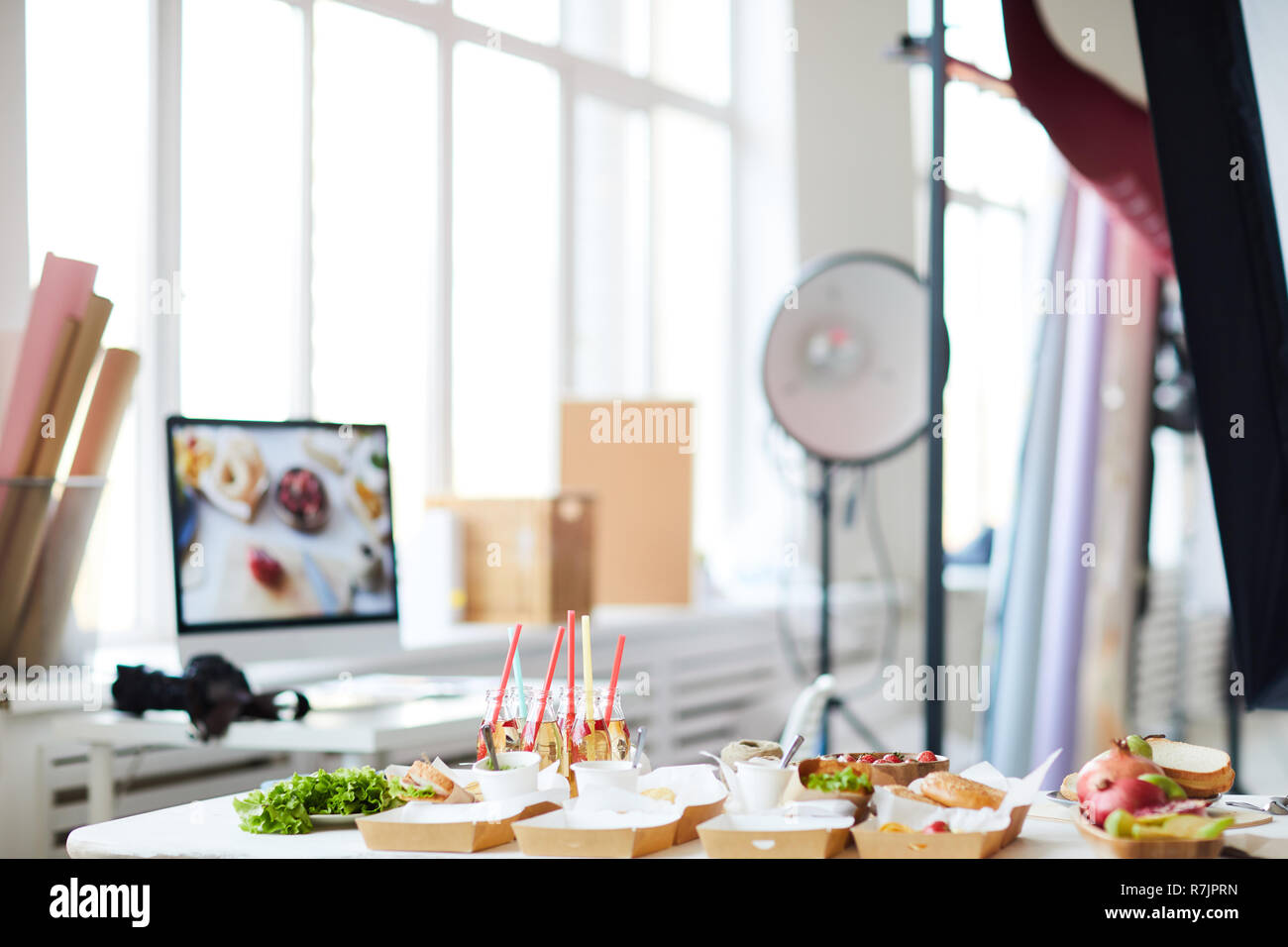 Background image of photo studio with party table with fast food in foreground, copy space Stock Photo