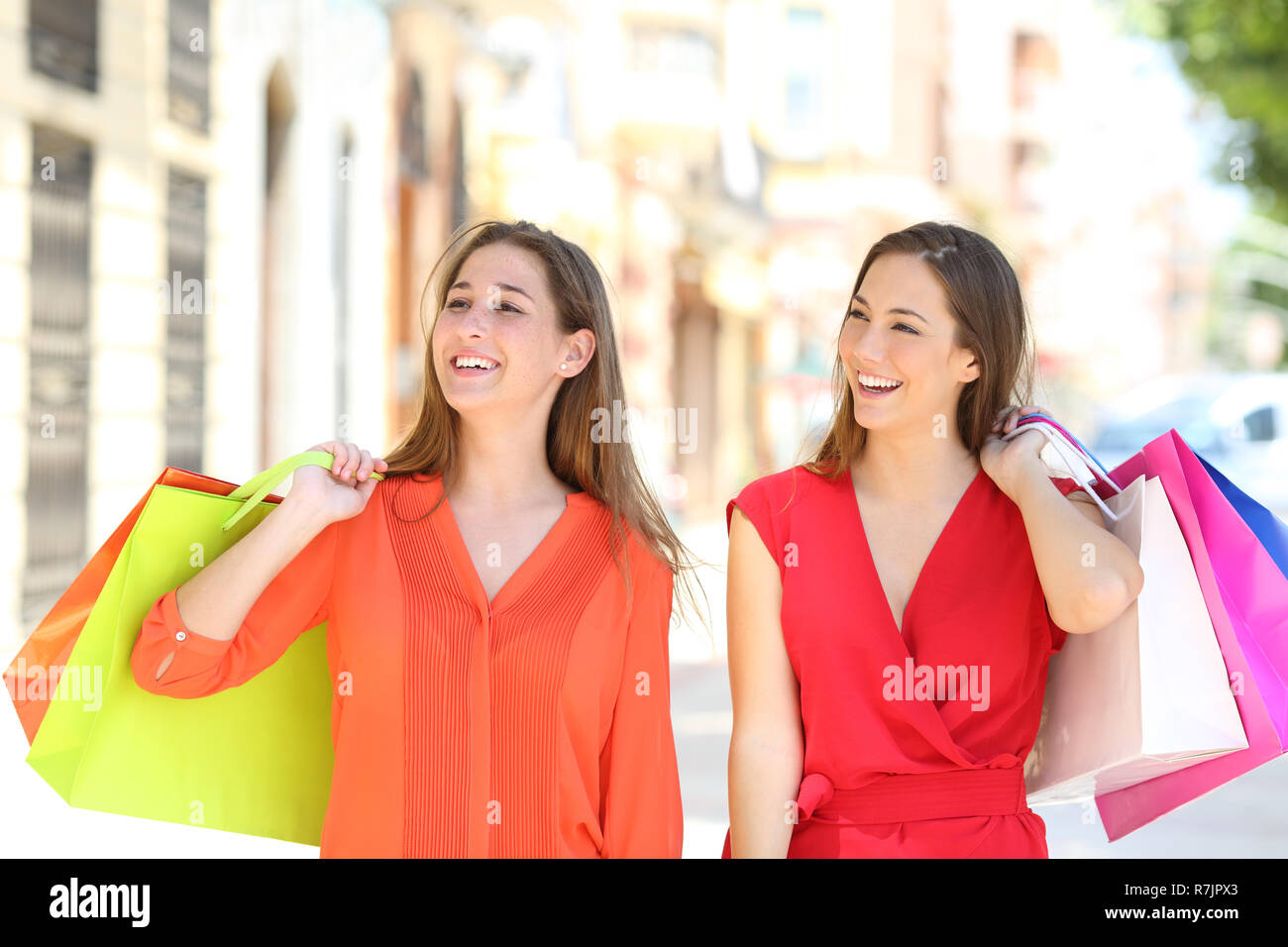 Front view portrait of two happy shoppers walking in an old town street holding shopping bags - Stock Image