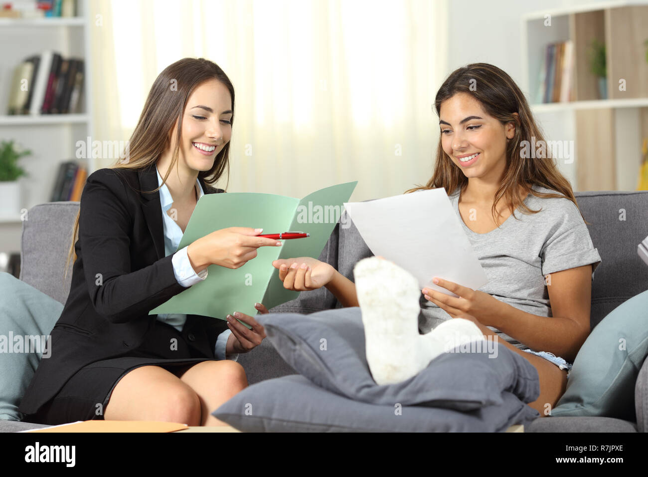 Happy insurance agent and disabled customer singing contract sititng on a couch at home - Stock Image
