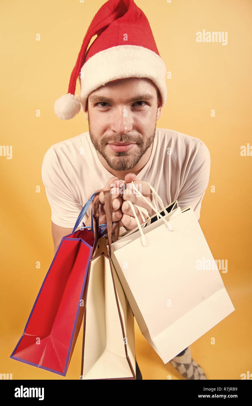 572e6ba6feb0c Black friday sale concept. Man shopper in santa hat with paperbags. New year