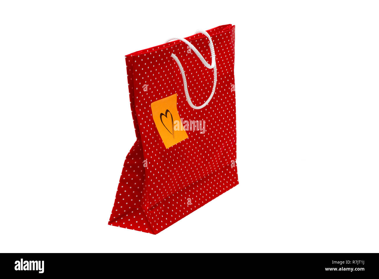 Gift bag with heart shape message, written by hand. Red polka dot paper bag isolated on white background. - Stock Image
