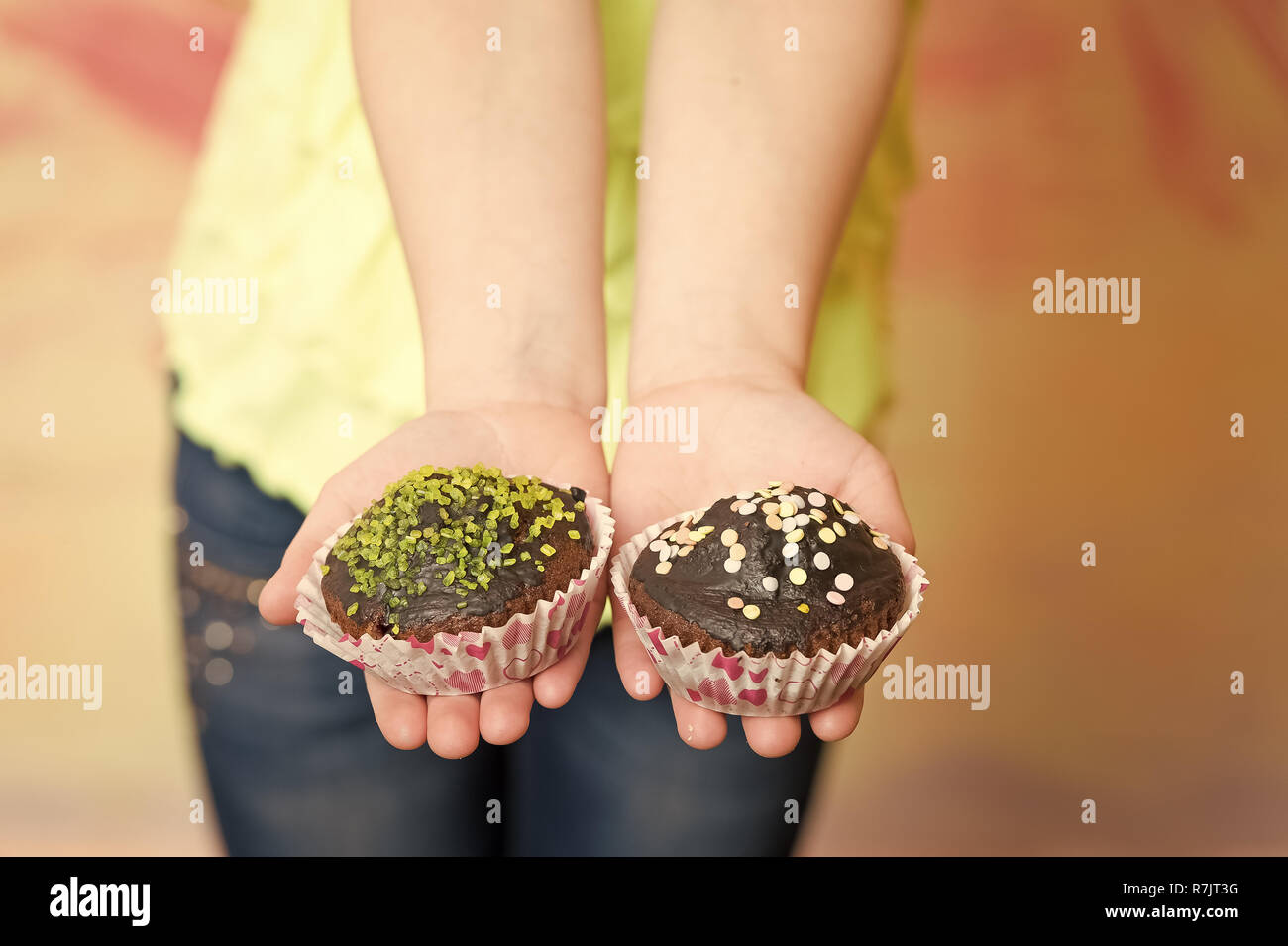 Two cupcakes of chocolate in childs hand on colorful blurred background. Confectionery, dessert, pastries, food, unhealthy diet concept. - Stock Image