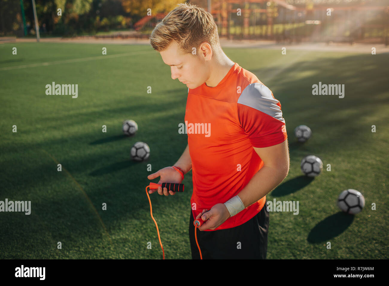 Young man in sport uniform is ready to exercise using jump rope. He looks down. Guy stand on green lawn. Five football balls are behind. - Stock Image