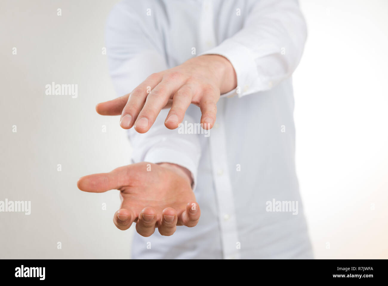 man with white shirt stretching out empty hand against white background - Stock Image