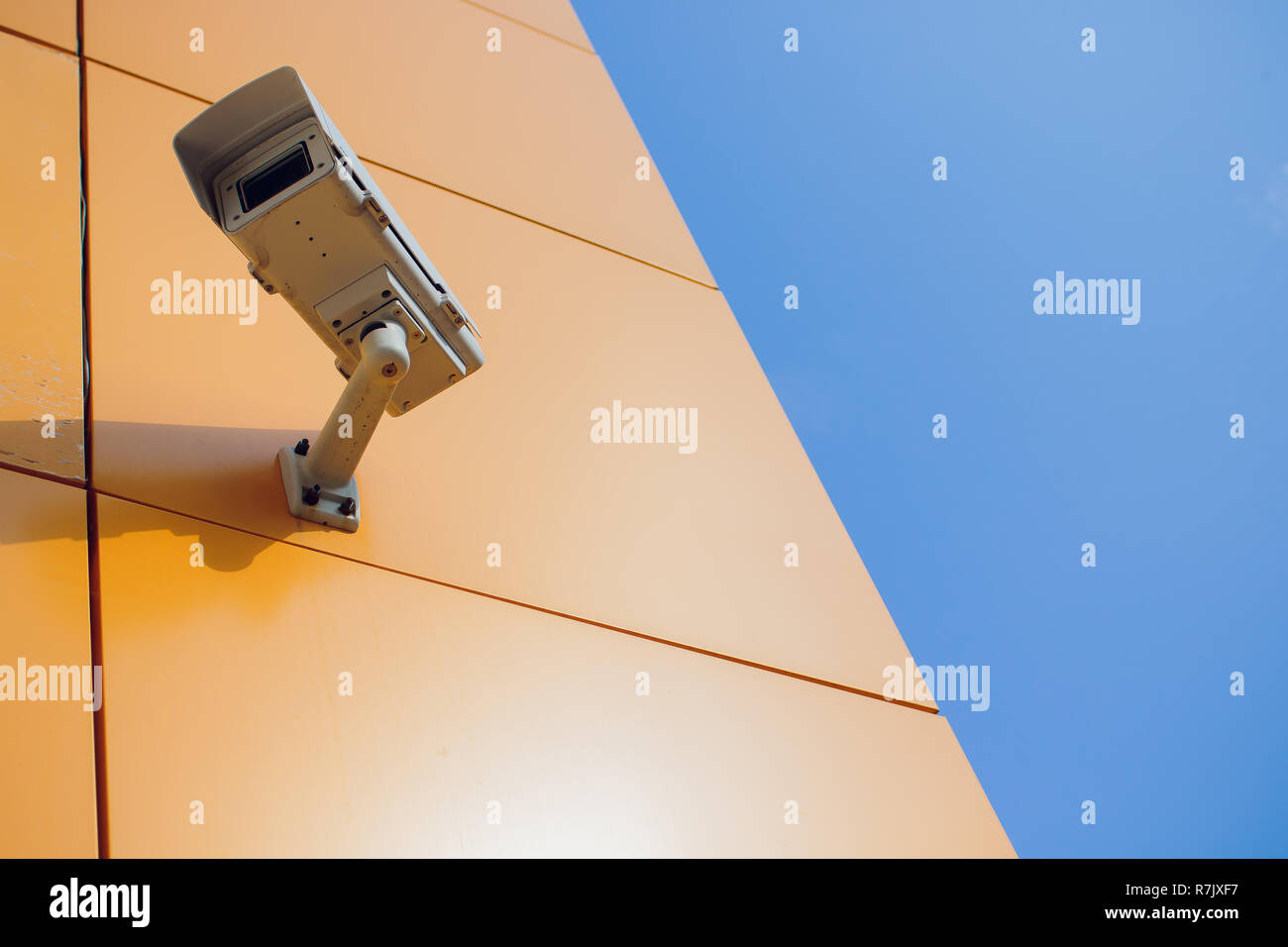 Modern CCTV camera on wall. A blurred night cityscape background. Concept of surveillance and monitoring. Toned image double exposure mock up - Stock Image