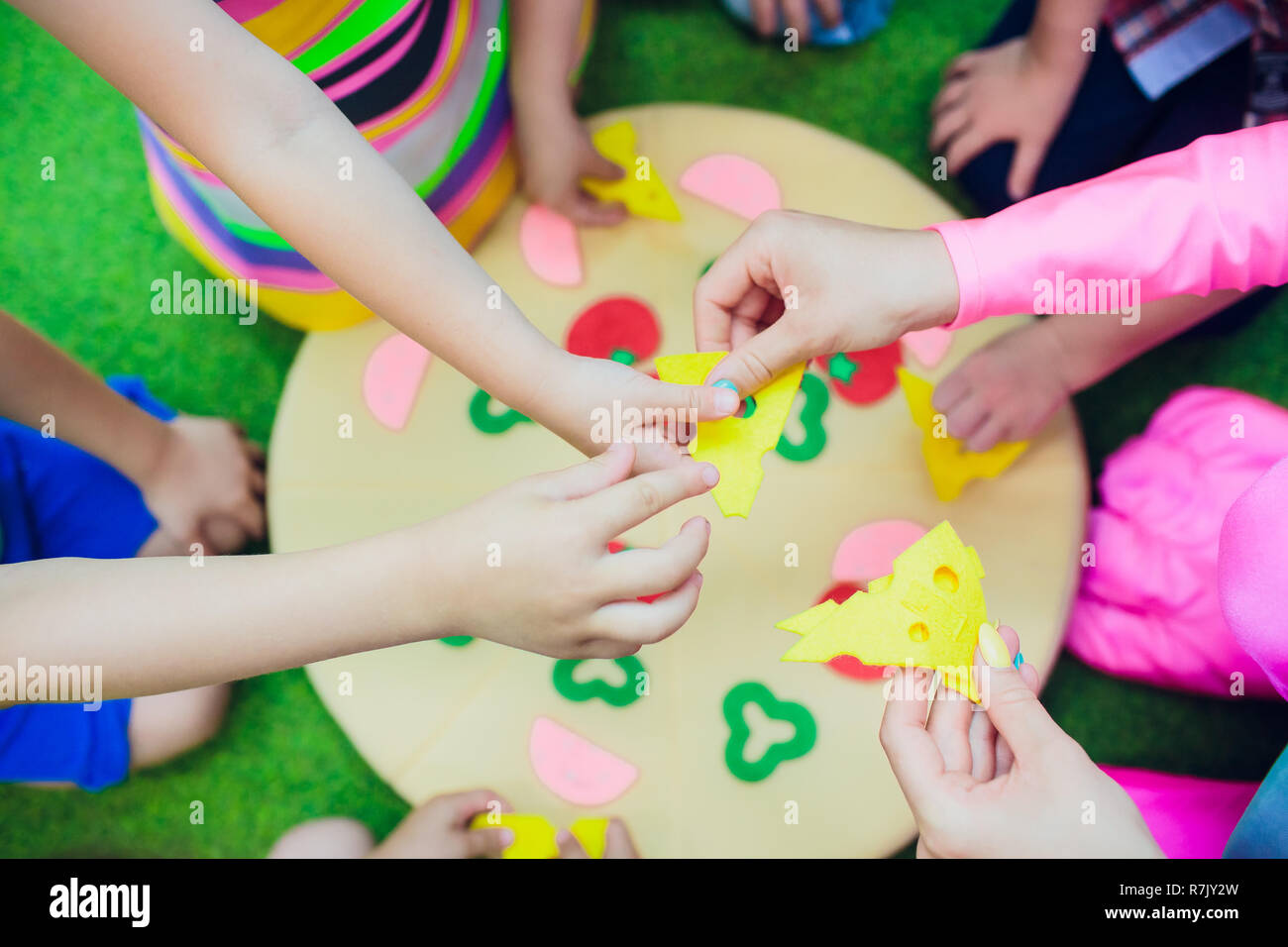 kids are playing. pillow pizza. The hands fastening with Velcro ingredients for pizza - Stock Image