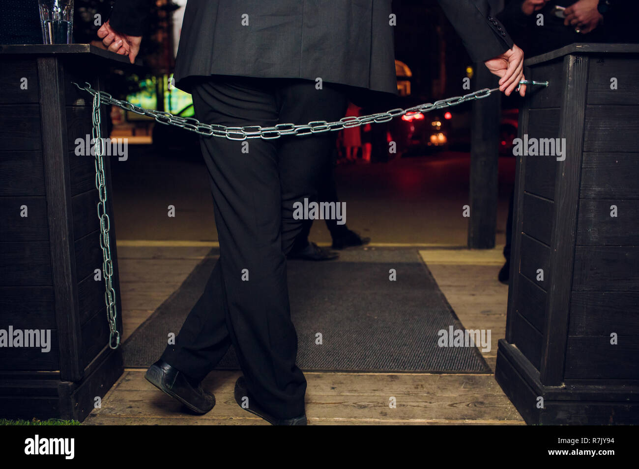security guard controlling indoor entrance gate - Stock Image