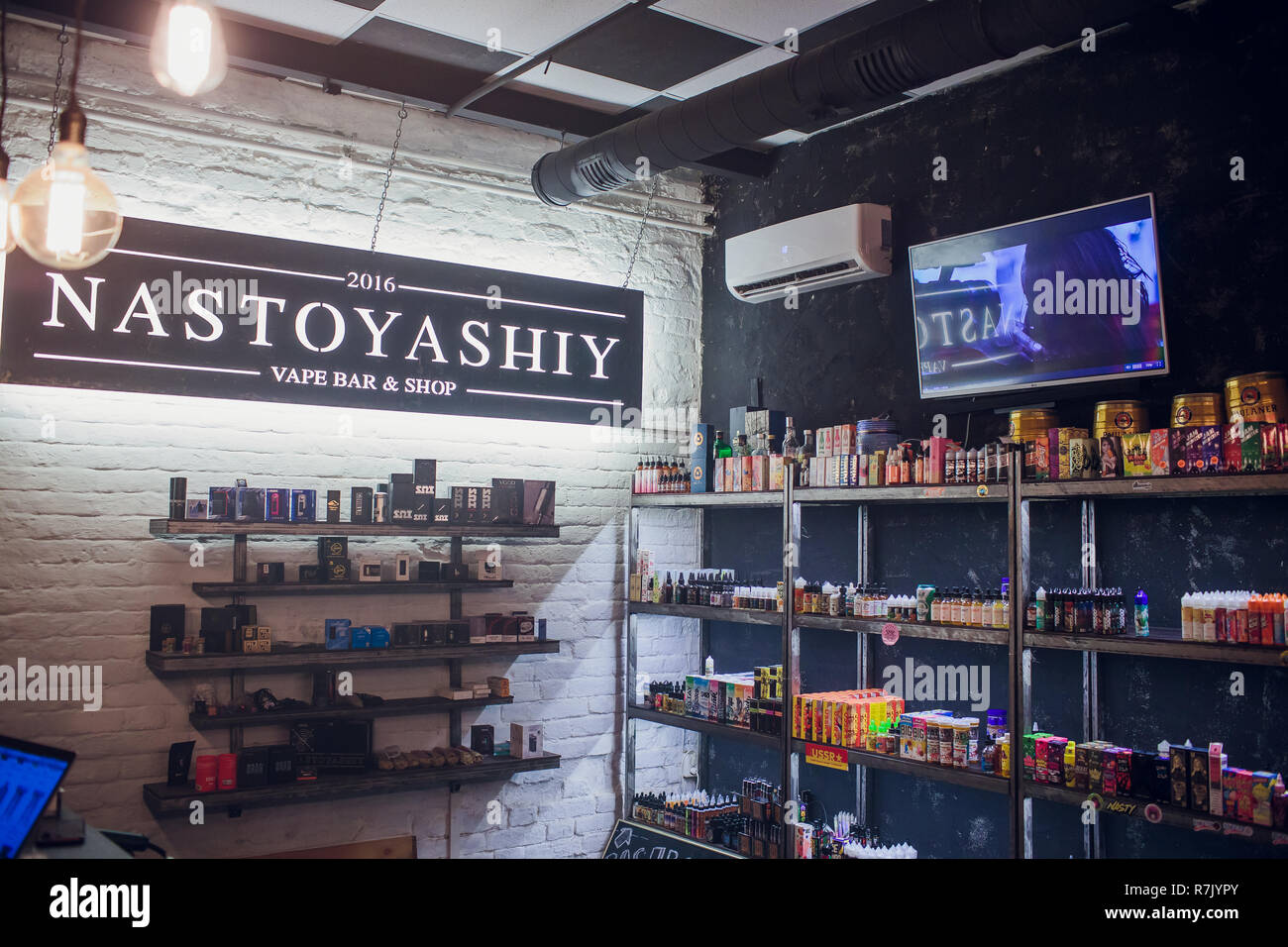 Ufa, Russia, South Vape Shop, 5 July, 2018: E-liquid e-juice High vape for electronic cigarette vaping device , on counter in smoke vapor in vape bar in bottles. - Stock Image