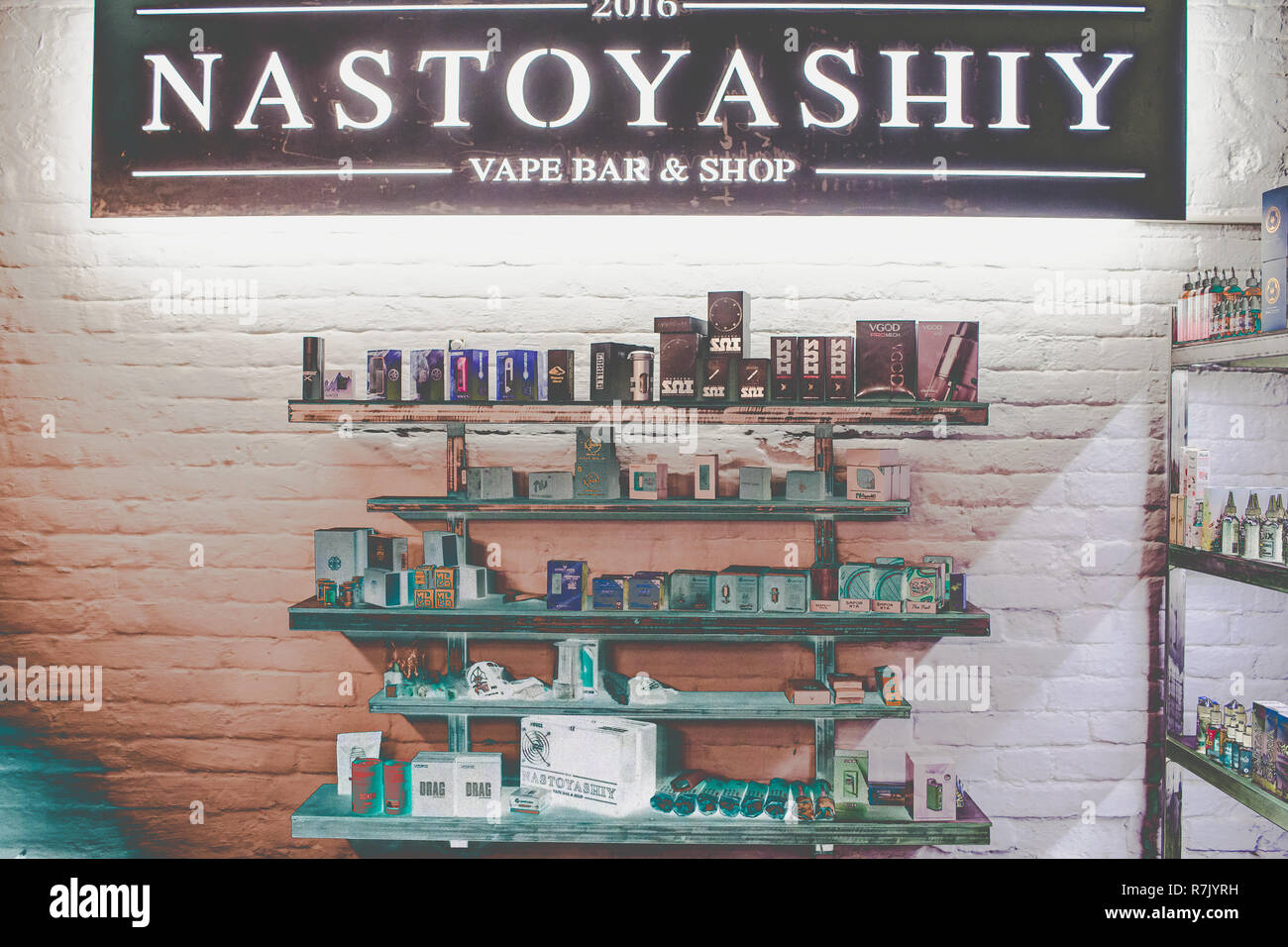Ufa, Russia, South Vape Shop, 5 July, 2018: E-liquid e-juice High vape for electronic cigarette vaping device , on counter in smoke vapor in vape bar in bottles. - Stock Image