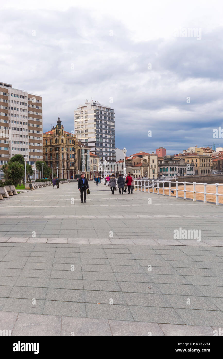 A view of San Lorenzo beach promenade  in Gijon Asturias Spain  in late autumn (fall) with an over cast sky and people walking on the sandy beach. - Stock Image