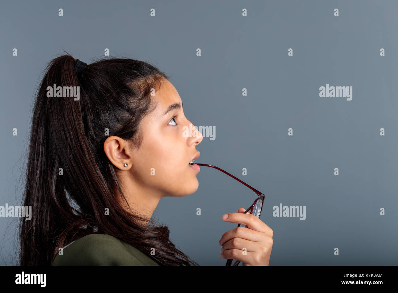 Teenage girl pondering with eyeglasses handle in mouth, profile view of brunette looking into space - Stock Image