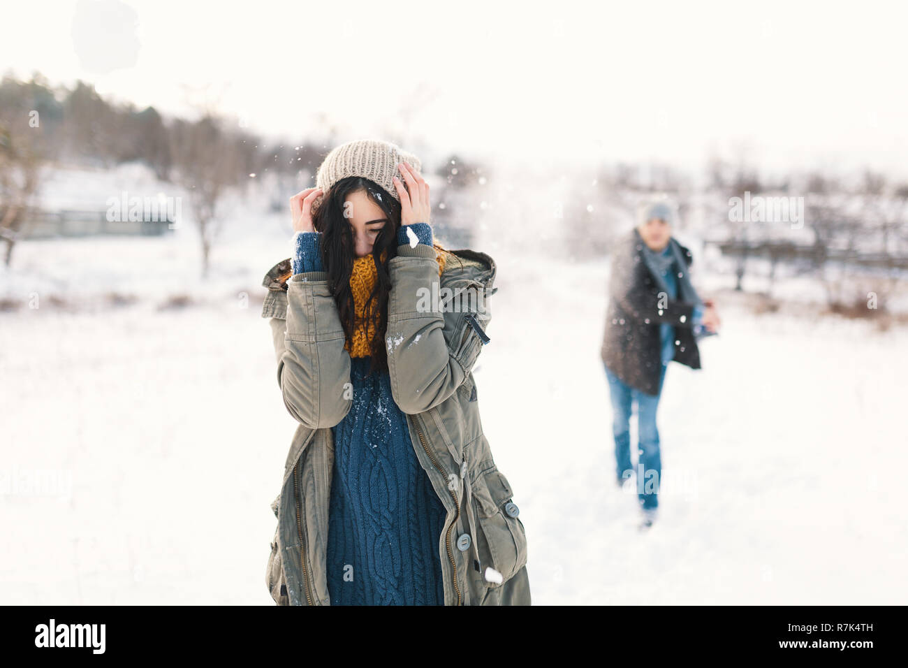 Snowball fight. Winter couple having fun playing in snow outdoors. Young joyful happy young man and woman. Stock Photo