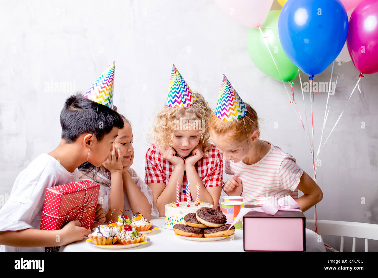 excited surprised rejoicing kids are gazering at cake - Stock Image
