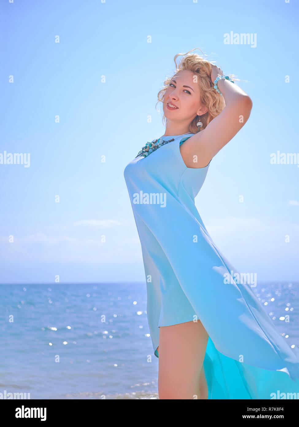 Stunning blondy woman in cyan dress on the beach - Stock Image