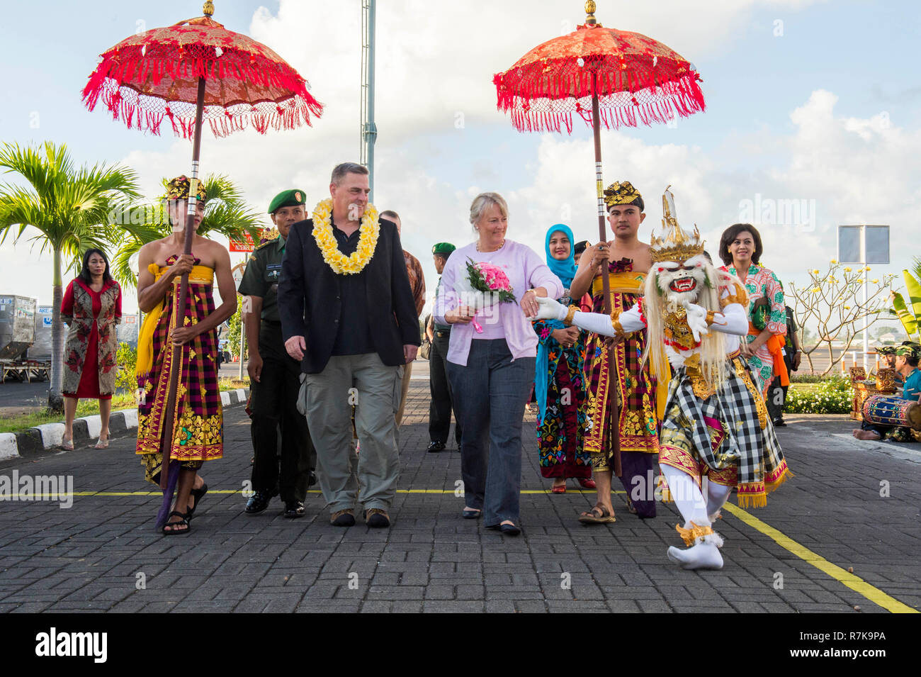 U.S. Army Chief of Staff Gen. Mark Milley, left, and his wife Hollyanne are welcomed by Balinese performers on arrival to Gusti Ngurah Rai International Airport September 13, 2015 in Bali, Indonesia. Milley was chosen by President Donald Trump on December 8, 2018 to be the next Chairman of the Joint Chiefs. - Stock Image