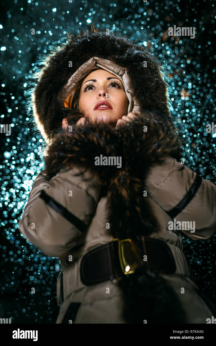 Beautiful young scared woman in winter jacket with fur hood worries and is looking away waiting for somebody. - Stock Image
