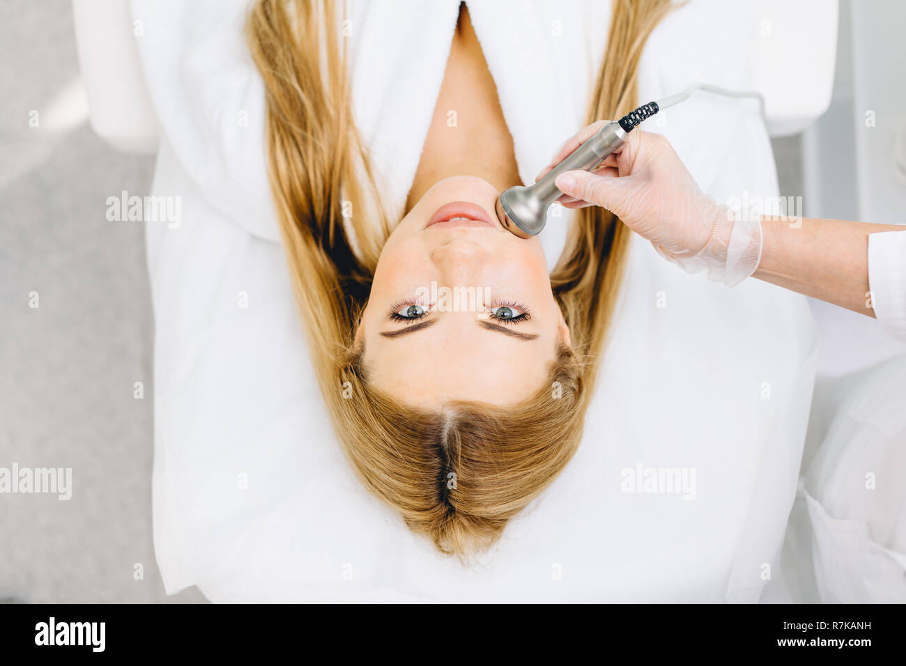 Blonde woman has ultrasonic dinamic lift massage in spa, hardware apparatus. - Stock Image