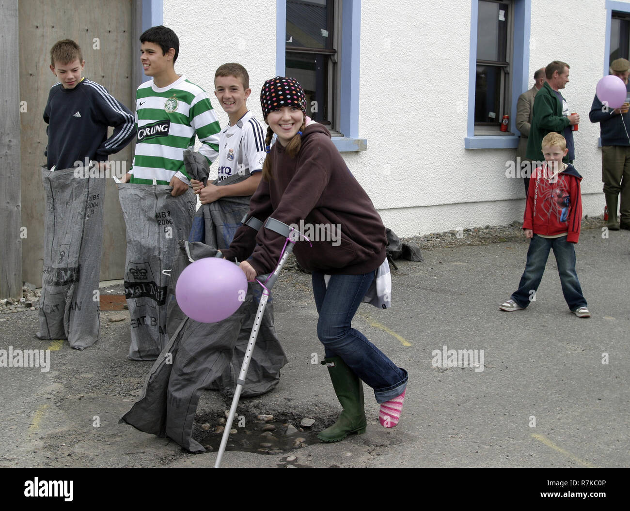 A rather optimistic girl, on crutches, enters the sack race at the small hamlet of Knoydart's gala day. Knoydart is a small, remote hamlet that sits on the Knoydart peninsula in the north west highlands in Scotland and can only be reached by boat or on foot. - Stock Image
