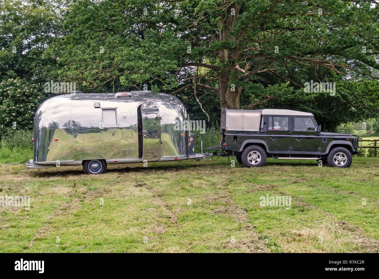 UK  Vintage Airstream caravan, towed by a Land Rover