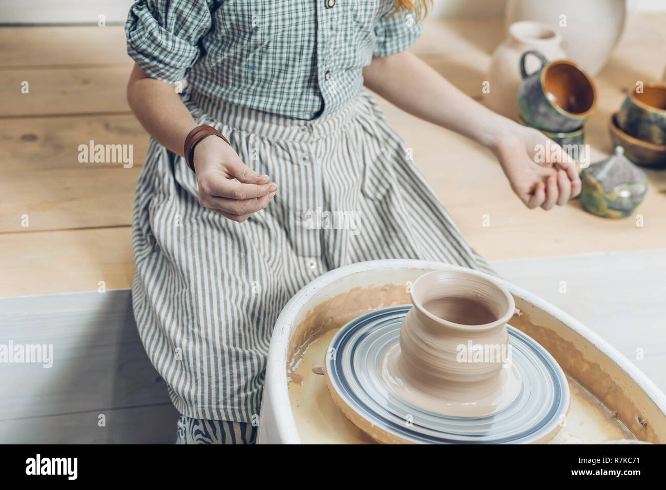 ready handmade pottery. woman has finished to make a pot - Stock Image
