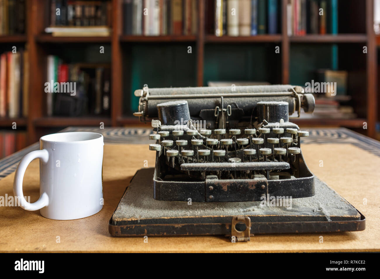 old vintage dust-covered typewriter and cup of coffee - Stock Image