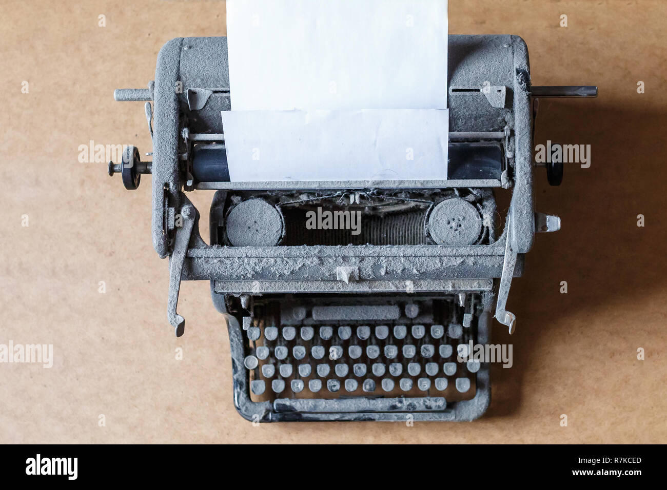 old vintage dust-covered typewriter with sheet of white paper - Stock Image