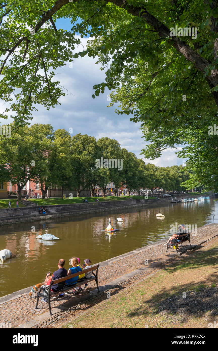 People sitting on the banks of the River Aura (Aurajoki) in the historic centre, Turku, Finland - Stock Image