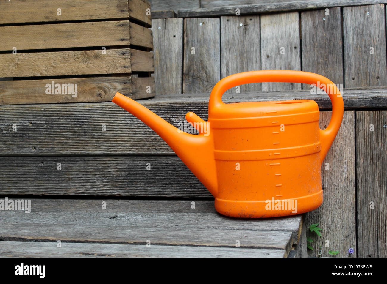 Orange watering can on wooden benches Stock Photo