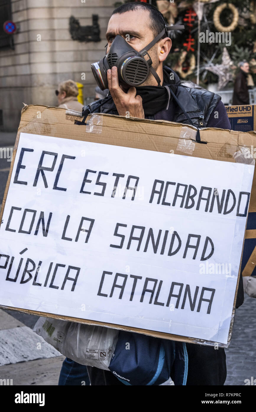 Barcelona, Catalonia, Spain. 10th December, 2018. A protester wearing a gas mask is seen holding a placard accusing ERC of the poor state of public health during the protest.Called by Marea Blanca Catalunya within the state fight against the waiting lists and the commercialization of health, the protesters have toured the center of Barcelona to finish in front of the Generalitat of Catalonia. Credit: Paco Freire/SOPA Images/ZUMA Wire/Alamy Live News - Stock Image