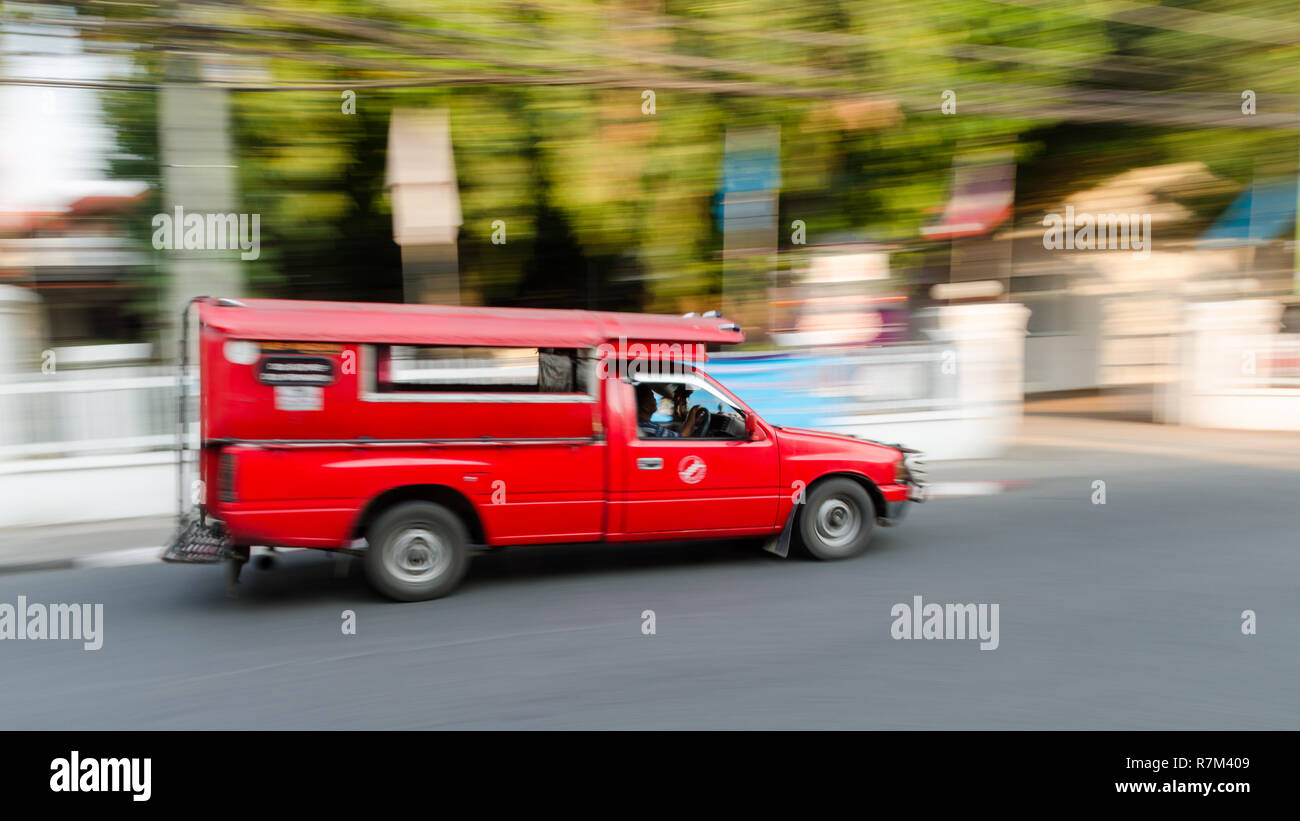Panning shot of a red songthaew in Chiang Mai, Thailand - Stock Image