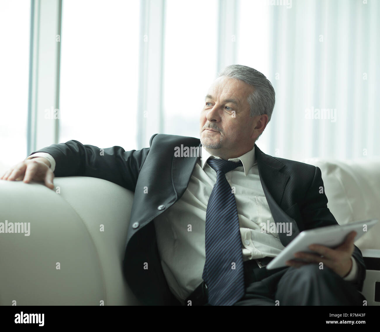 responsible businessman sitting in modern office.people and technology - Stock Image