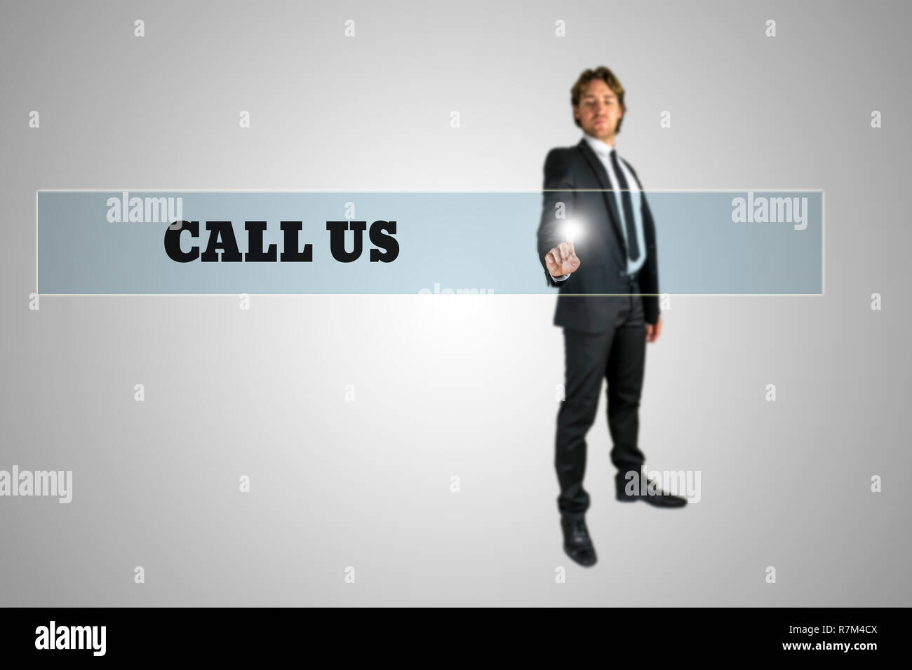 Businessman touching - Call us - navigation bar on a virtual screen with his finger from behind in a conceptual image. - Stock Image