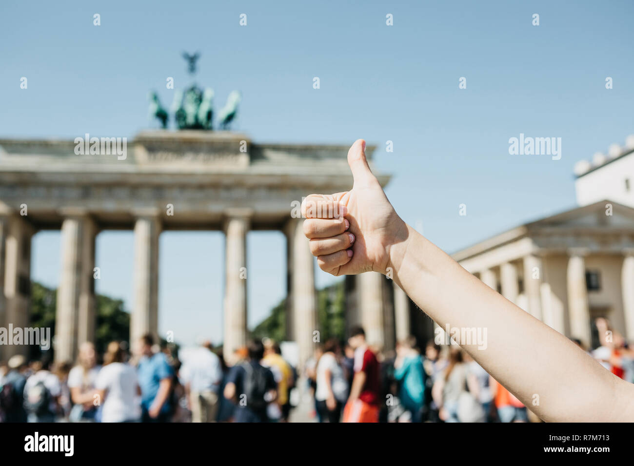 A person shows a sign with a finger upwards meaning everything is okay or confirms against the background of the Brandenburg Gate and blurred unrecognizable people in Berlin in Germany. - Stock Image