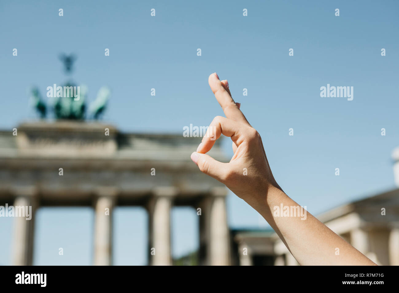 A person shows a sign with his fingers that means everything is good against the background of the Brandenburg Gate and blurry unrecognizable people in Berlin in Germany. - Stock Image
