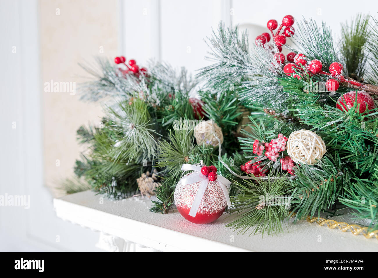Christmas decoration of holly berry and pine cone.Christmas background. Green branches with red berries. Home decor for holidays. decoration balls with fir cones and fir branches, white candle. - Stock Image