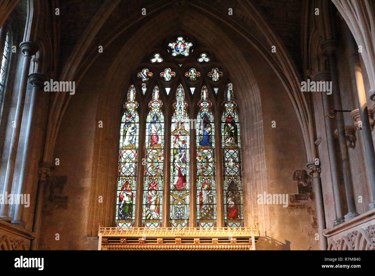 A pointed arch, stained glass window with Gothic decorations