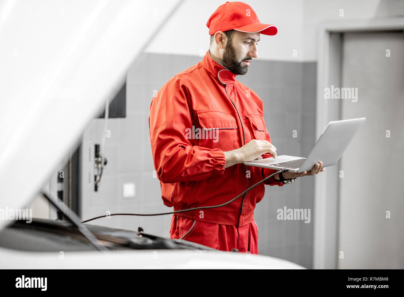 Two auto mechanics in red uniform doing engine diagnostics with computer in the car service - Stock Image