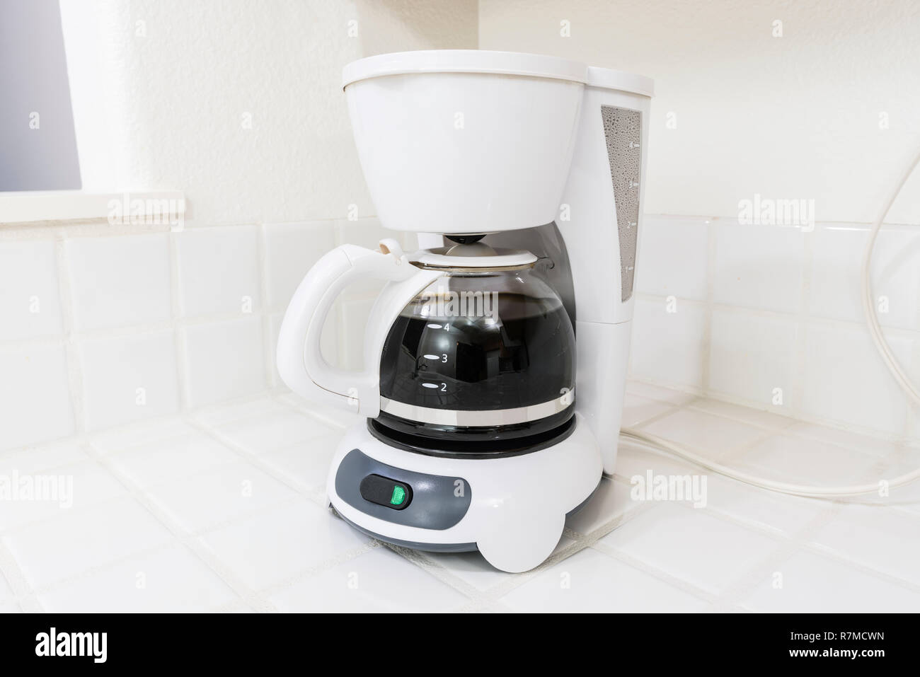 White coffee maker brewing on clean white tile kitchen counter. - Stock Image