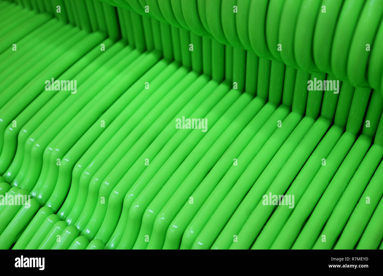 Lined Up Empty Vivid Green Clothes Hangers - Stock Image