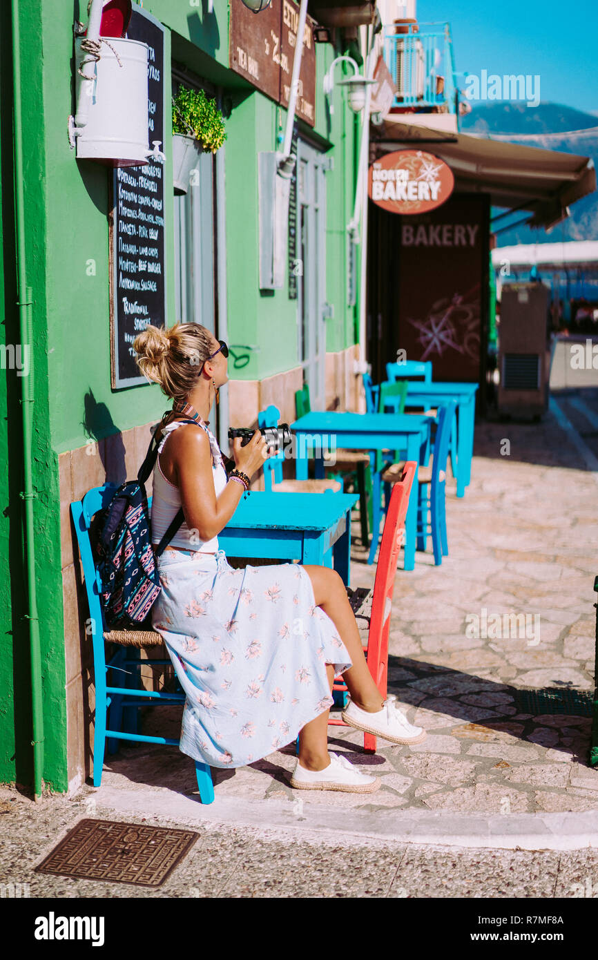 Tanned young woman with camera on vacation in Greece exploring cozy narrow alleys in greek town. Lovely exited girl sitting in street cafe and enjoying summer day. European holidays concept - Stock Image