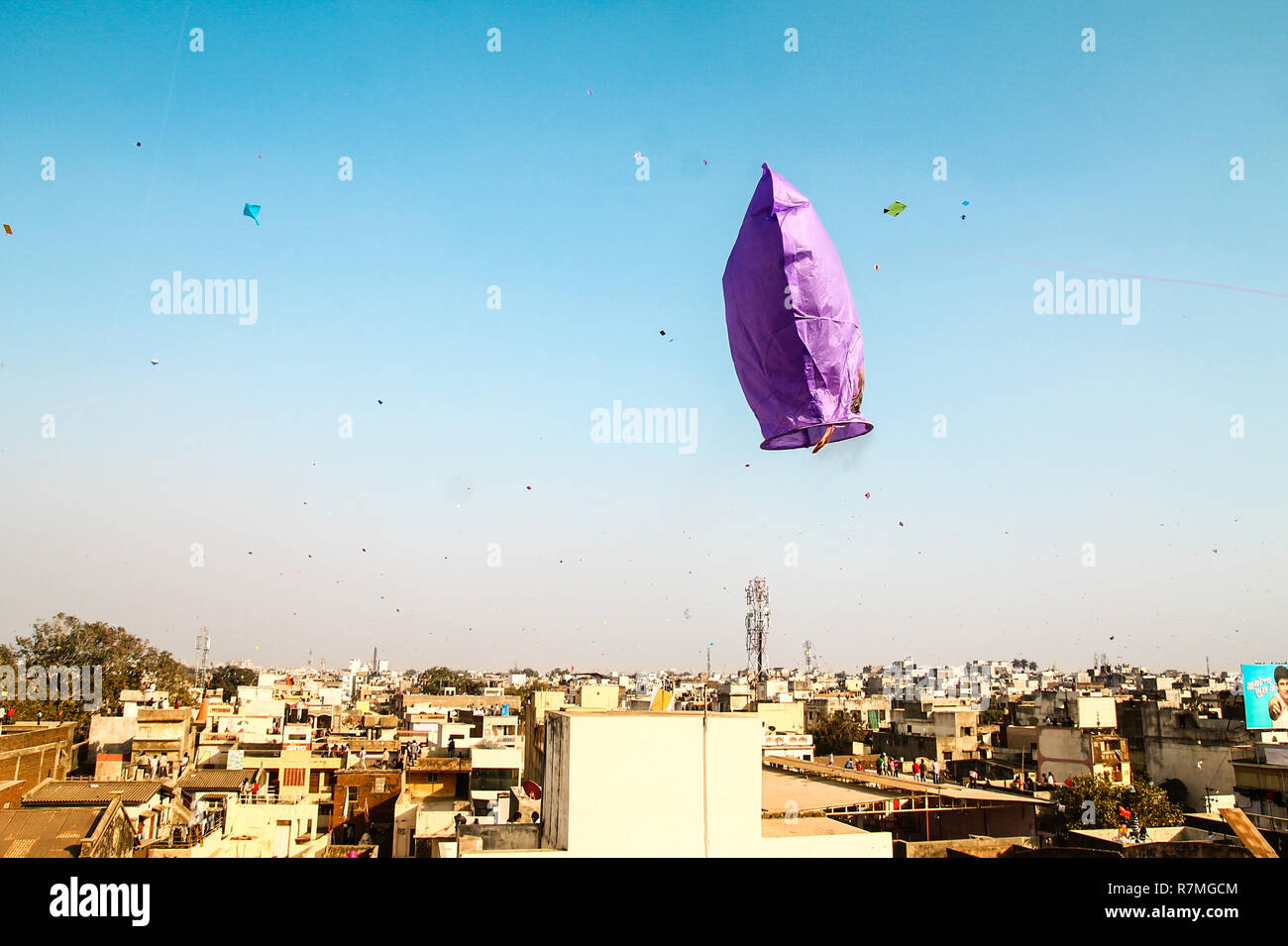 fire kite flying over clear blue sky during traditional hindu kite festival in indian city Stock Photo