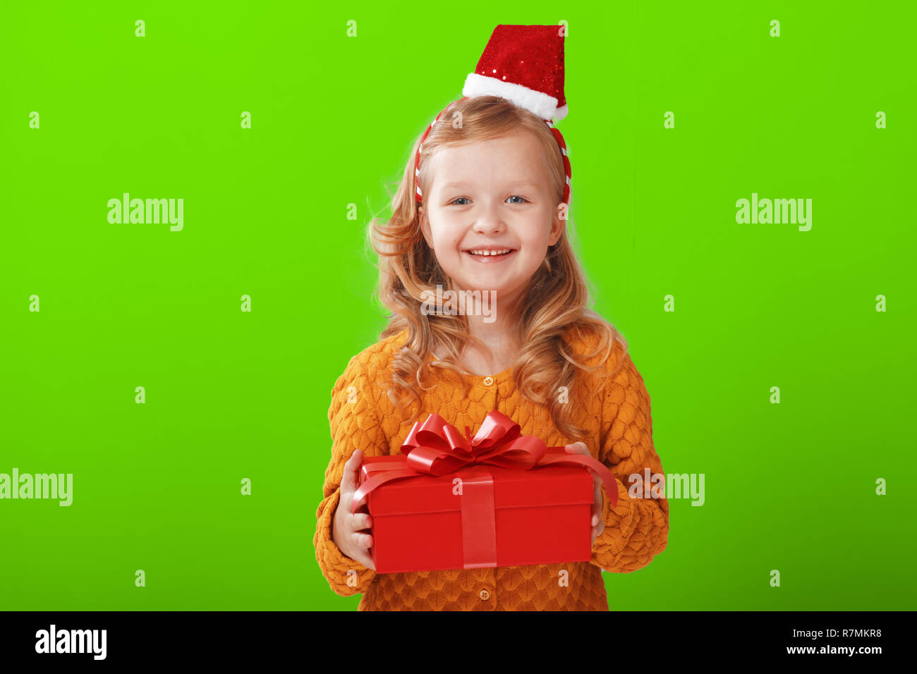 ea862204150 Happy little child girl in a warm knitted sweater and cap Santa Claus is  holding a