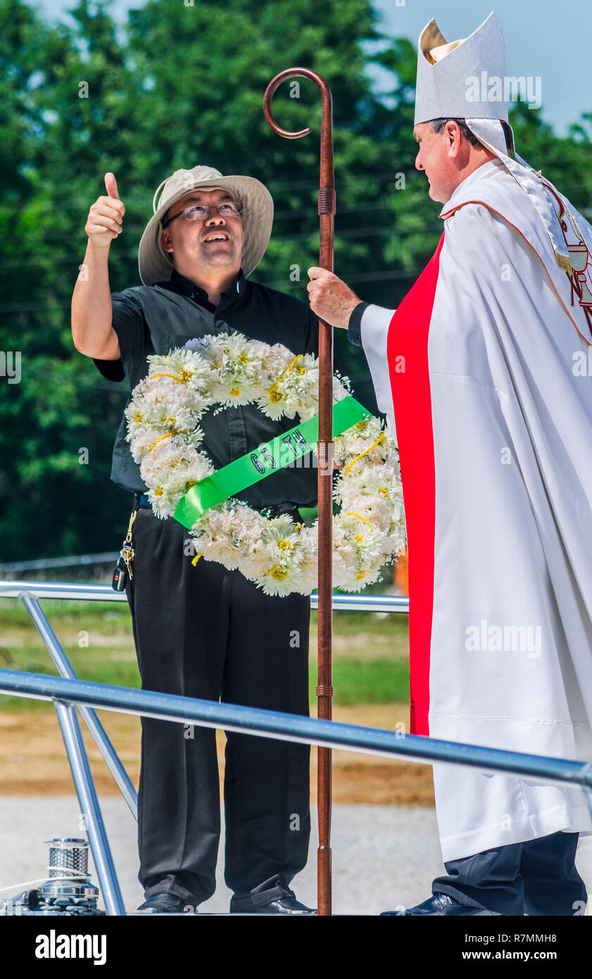 Rev. Bieu Nguyen holds a ceremonial wreath as he talks to Catholic Archbishop Thomas J. Rodi at the Blessing of the Fleet in Bayou La Batre, Alabama. - Stock Image