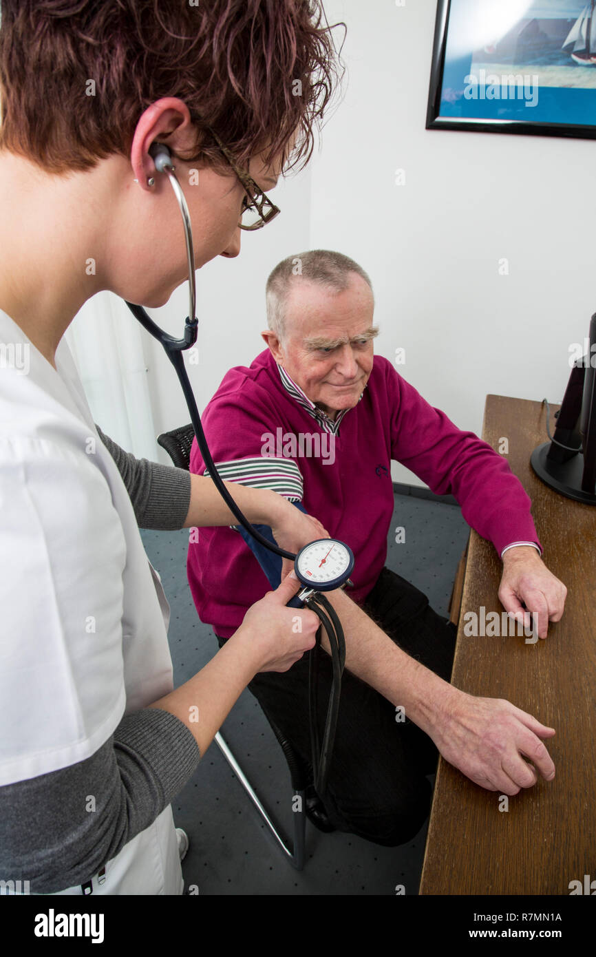 Doctor's office, older patient gets his blood pressure taken by a doctor's assistant, Germany - Stock Image