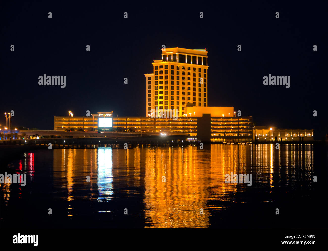 The Beau Rivage Casino Is Lit At Night And Reflected In The Water