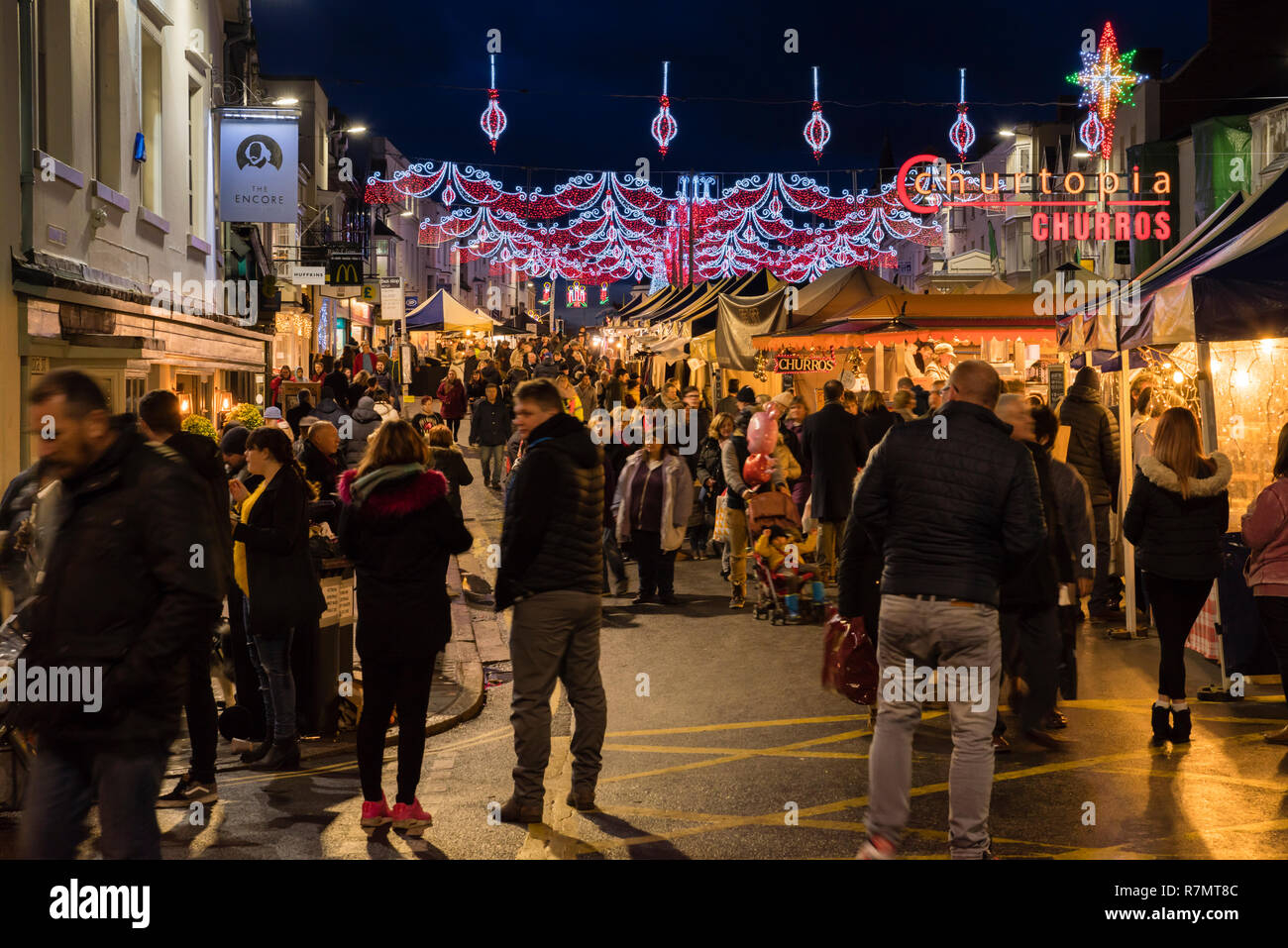 Crowds at the Victorian Christmas Market and lights at night, Bridge Street, Stratford upon Avon, England Stock Photo