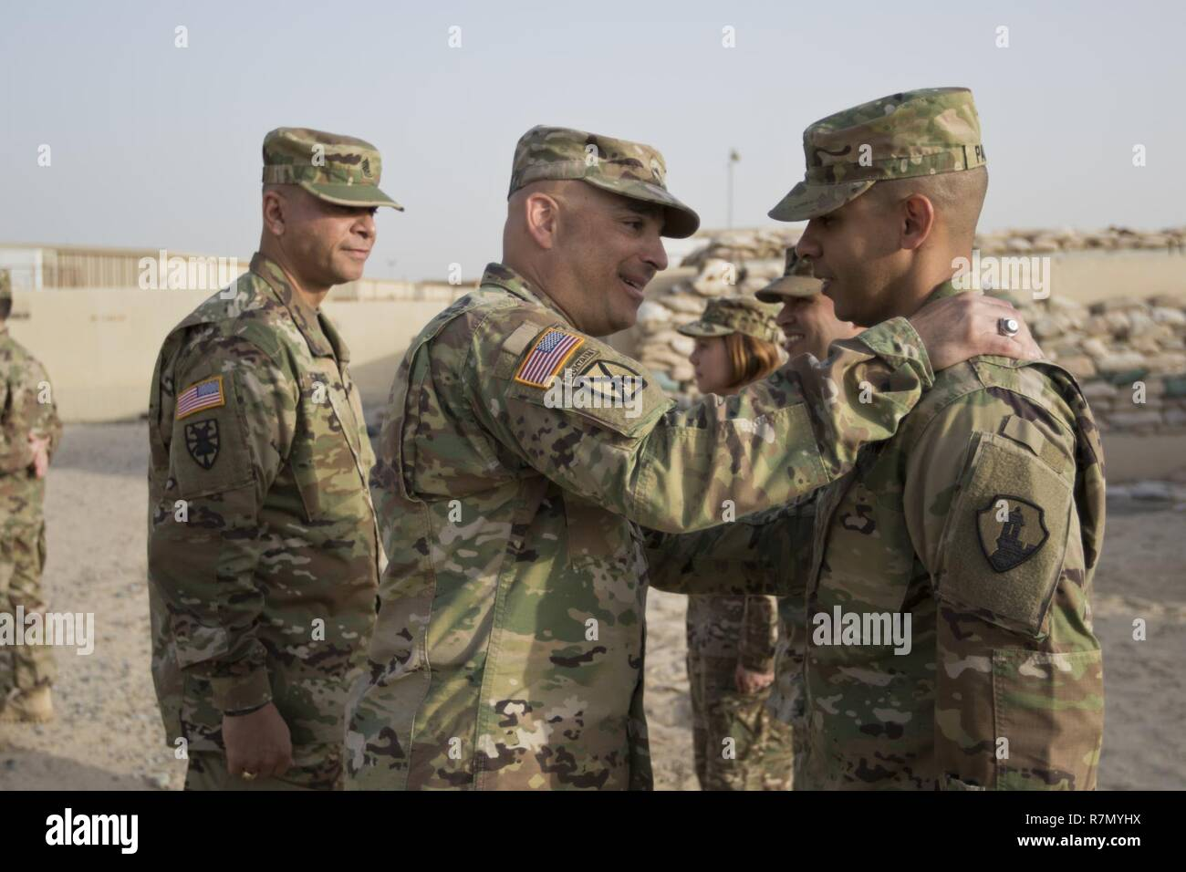 Brig. Gen. Alberto Rosende, commanding general of the 1st Mission Support Command, an Army Reserve unit based out of Fort Buchanan, Puerto Rico, slaps the Garita patch on a Soldier during a patching ceremony for the 246th Quartermaster Company (Mortuary Affairs) at Camp Arifjan, Kuwait, on Mar. 20, 2017. - Stock Image